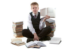 The schoolboy in a school uniform sits on a floor. Near to packs of books, with the opened book in hands Royalty Free Stock Images
