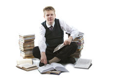 The schoolboy in a school uniform sits on a floor, near to packs of books, with the opened book in hands.  Stock Photo