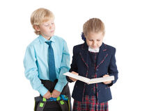 Schoolboy with schoolbag in hands standing near the schoolgirl while she reading book, isolated white background Stock Photo
