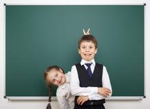 Schoolboy and schoolgirl near the school board Stock Photo