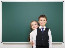 Schoolboy and schoolgirl near the school board Royalty Free Stock Photo