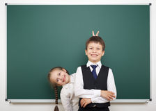 Schoolboy and schoolgirl near the school board Stock Photos