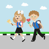 Schoolboy and schoolgirl with satchels. Girl with a bow and a bell. Boy with flowers go in the first class. Flat Stock Photos