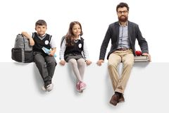 Schoolboy, schoolgirl and a teacher sitting on a panel Stock Photos