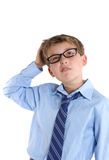 Schoolboy scratching head while thinking and looking up stock photography