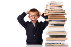 Schoolboy screaming near the huge stack of books Royalty Free Stock Images