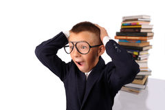 Schoolboy screaming near the huge stack of books Royalty Free Stock Photos