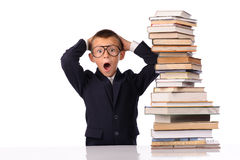 Schoolboy screaming near the huge stack of books Royalty Free Stock Photography
