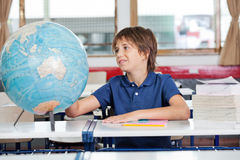 Schoolboy Searching Places On Globe At Desk Royalty Free Stock Photos