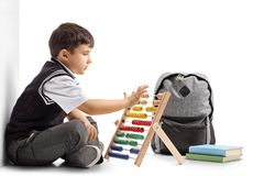 Schoolboy seated on the floor using an abacus Royalty Free Stock Images