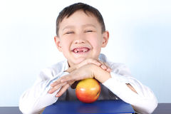 Schoolboy without several tooth's with apple Stock Image