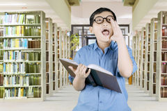 Schoolboy shouting while holding a textbook Royalty Free Stock Photography