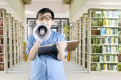 Schoolboy shouting on megaphone. Portrait of schoolboy is shouting on megaphone and holding a textbook while standing in library Royalty Free Stock Images
