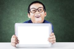 Schoolboy showing blank screen of digital tablet. Picture of adorable schoolboy showing blank screen of digital tablet while sitting with funny expression face Royalty Free Stock Photo