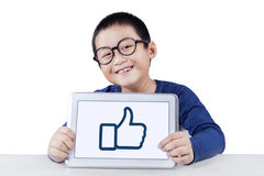 Schoolboy showing thumb up icon with tablet Stock Photography
