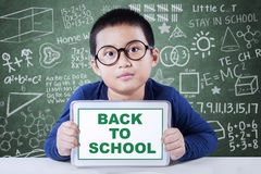 Schoolboy shows a text of back to school in class Royalty Free Stock Photography