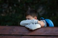 Schoolboy sits on a bench at a school park and cries. Negative emotion royalty free stock photos