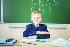Schoolboy sits at a desk at school classroom Stock Photo