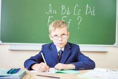 Schoolboy sits at a desk at school classroom Royalty Free Stock Image