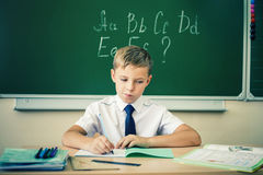 Schoolboy sits at a desk at school classroom. Boy thinking and sits at a desk at school with glasses and writes in a notebook. Against the background of the Stock Image