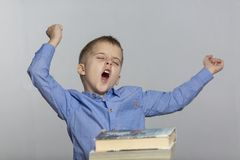 A schoolboy sits at a table with books, yawns and sips. Gray background royalty free stock photography