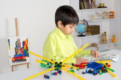The boy sits in the nursery and the designer collects Stock Photo