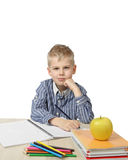 Schoolboy. Sits thoughtful with chin rested on fist near the desk with school supplies and big apple on foreground isolated on white background - ponders lesson Royalty Free Stock Photo