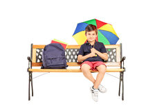 Schoolboy sitting on a bench and holding colorful umbrella Stock Photo