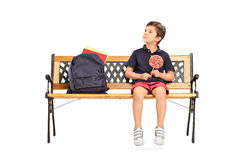 Schoolboy sitting on a bench and holding lollipop Stock Photos
