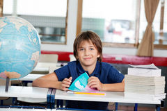 Schoolboy Sitting With Books And Globe At Desk Royalty Free Stock Image