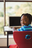 Schoolboy sitting on chair and using laptop at school Stock Photo