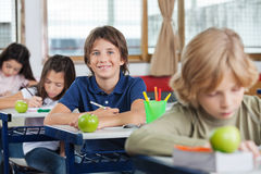 Schoolboy Sitting At Desk With Classmates In A Row Royalty Free Stock Image