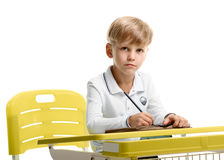Schoolboy sitting at the desk. Portrait of little schoolboy sitting at the desk and doing homework Stock Photos