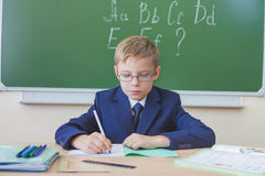 Schoolboy sitting at desk at school and writing to notebook Royalty Free Stock Image