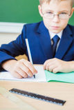 Schoolboy sitting at desk at school and writing to notebook Stock Photo