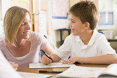 A schoolboy sitting with his teacher in class Stock Image
