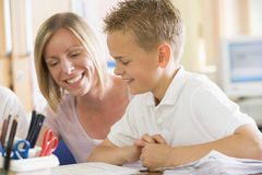 A schoolboy sitting with his teacher in class Stock Images