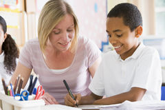 A schoolboy sitting with his teacher in class Royalty Free Stock Photo