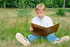 Schoolboy sitting in the park and reading a book Stock Photo