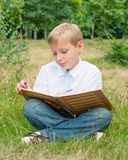 Schoolboy sitting in the park and writing in a notebook Stock Photo