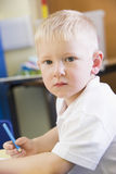 A schoolboy sitting in a primary class stock image