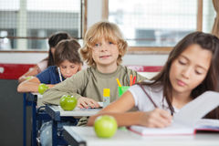 Schoolboy Sitting In A Row With Classmates At Stock Images