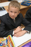 Schoolboy sitting in school. Schoolboy in suit sitting on the lecture at desk Royalty Free Stock Images