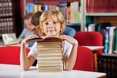 Schoolboy Sitting With Stack Of Books In Library Stock Images