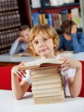 Schoolboy Sitting With Stack Of Books At Table In. Portrait of cute little schoolboy sitting with stack of books at table in library and classmates in background Stock Image