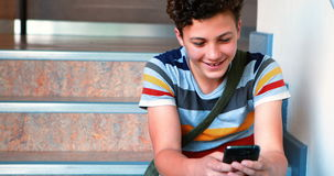 Schoolboy sitting on staircase and using mobile phone. At school stock video footage