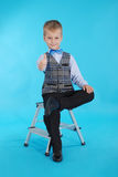 Schoolboy sitting on a stepladder and showing thumbs up Stock Image