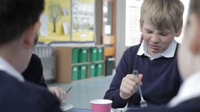 Schoolboy Sitting At Table Eating Lunch stock video