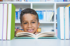 Schoolboy sitting on table and reading book in library Stock Photo