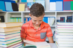 Schoolboy sitting on table and reading book in library Stock Photos